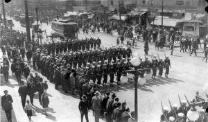 Three sections of armed sailors marching through a city.
